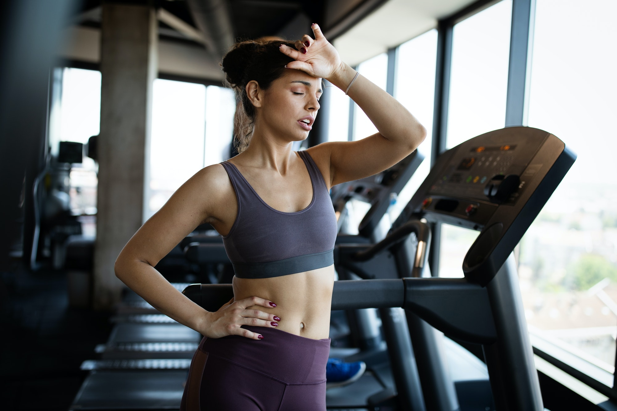 Fitness woman. Beautiful young girl in the gym on the treadmill. Fatigue, hand in head, wipes sweat